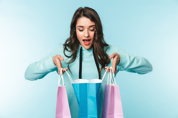 Ritratto di una bella giovane donna bruna eccitata in piedi sul blu, portando le borse della spesa