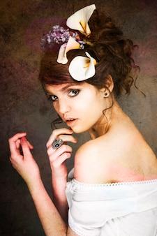 Ritratto di bella modella con grandi fiori in acconciatura