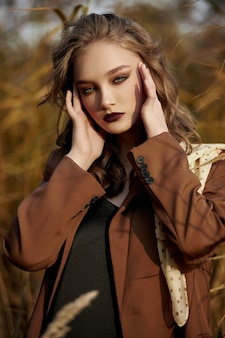 Ritratto di una donna bellissima moda in un boschetto di erba autunnale