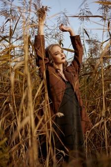 Ritratto di una bella donna di moda in un boschetto di erba autunnale