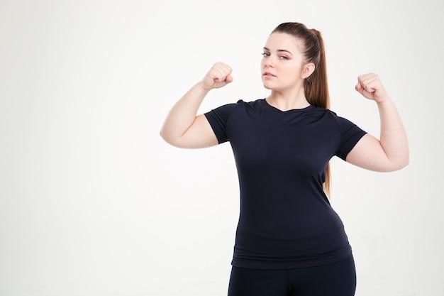 Ritratto di una bella donna grassa che mostra i suoi bicipiti isolati su un muro bianco