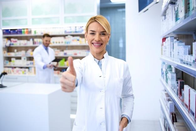 Ritratto di bella femmina bionda farmacista alzando i pollici in farmacia o in farmacia.