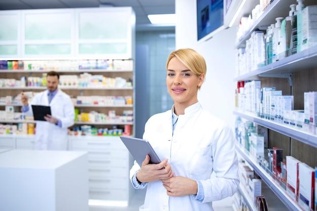 Ritratto di bella femmina bionda farmacista in piedi in farmacia o in farmacia dallo scaffale con farmaci e tenendo la compressa.