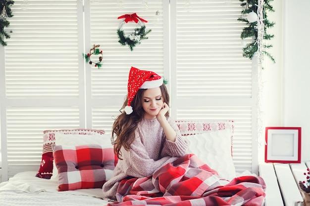 Ritratto di bella modella femminile in cappello della santa a letto. concetto di natale