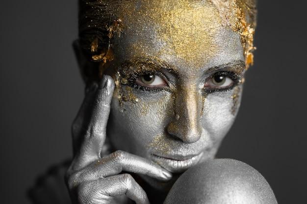 Ritratto di una bellissima modella con vernice oro e argento sulla pelle e sui capelli in studio.