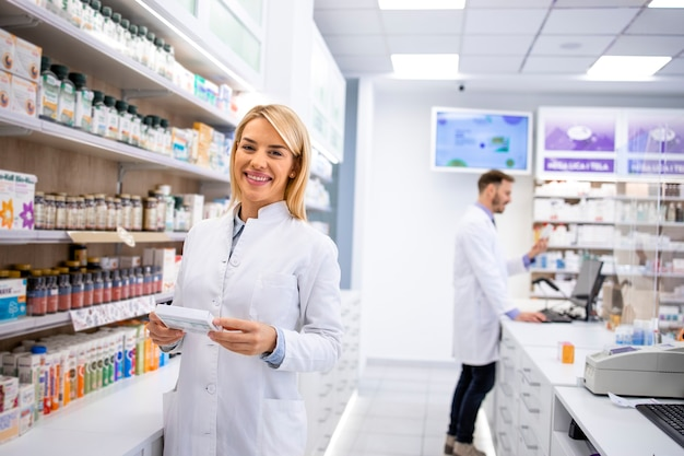 Ritratto di bella donna farmacista in piedi nel negozio di farmacia dallo scaffale con farmaci.