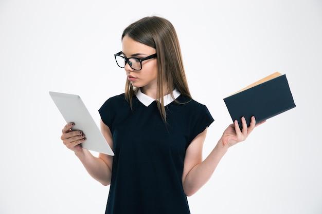 Ritratto di una bellissima studentessa che sceglie tra tablet e libro isolato