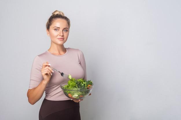 Ritratto di bella donna in forma con chignon che tiene in mano un grido di insalata di verdure fresche e che guarda l'obbiettivo, dieta vegetariana, cibo sano, copia spazio per la pubblicità. foto in studio, sfondo grigio