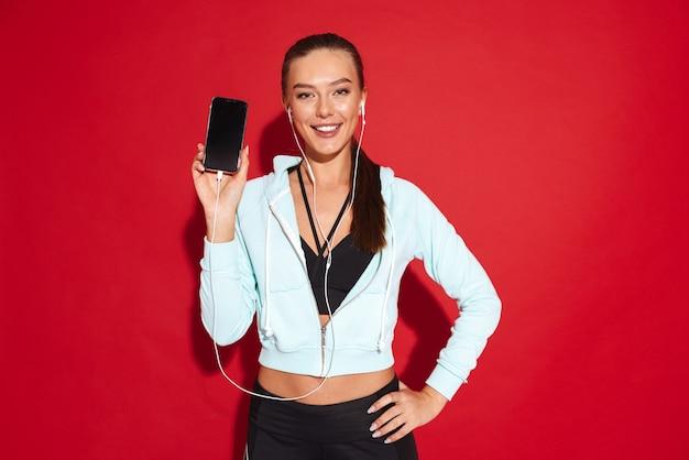 Ritratto di una bella giovane sportiva in forma in piedi, mostrando il telefono cellulare con schermo vuoto