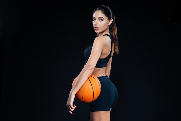 Ritratto di una bella donna fitness che tiene in mano una palla da basket e guarda la telecamera su sfondo nero