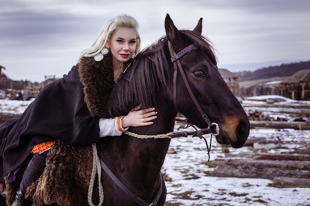 Ritratto di bella donna scandinava furiosa in abiti tradizionali, villaggio vichingo