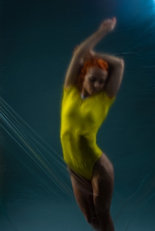 Ritratto di una bella ragazza atleta in un body giallo su sfondo scuro.