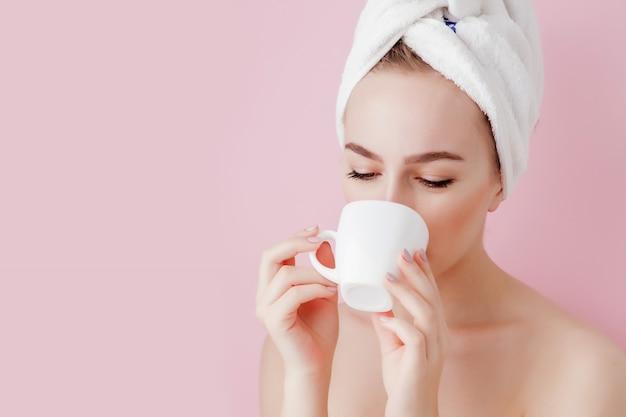 Ritratto di una bella ragazza in accappatoio con una tazza di tè, relax concetto donna bionda che indossa accappatoio e asciugamano sulla testa dopo la doccia. donna della stazione termale in accappatoio e turbante
