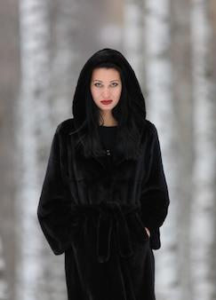 Ritratto di una bella ragazza con un cappotto di visone nero