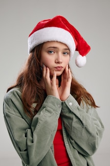 Ritratto di una bella ragazza in un cappello festivo natale capodanno gesticolare con le mani
