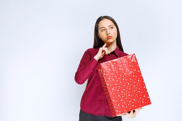 Ritratto di una bella ragazza che tiene la scatola presente e distoglie lo sguardo sul muro bianco.