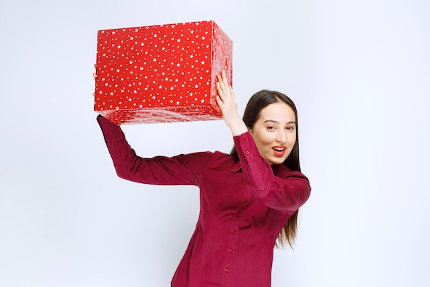 Ritratto di una bella ragazza che tiene la scatola presente sul muro bianco.