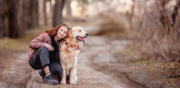 Ritratto di bella ragazza che abbraccia il cane golden retriever nel legno e sorridente