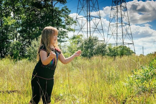 Ritratto di una bella ragazza sulla natura. il campo di camomilla. piccole margherite con bouquet di fiori in piedi sullo sfondo del cielo blu