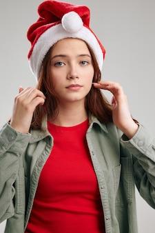 Ritratto di una bella ragazza in giacca e cappello di capodanno su uno sfondo grigio natale. foto di alta qualità