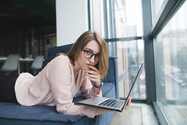 Ritratto di una bella ragazza in ufficio su un divano con un computer portatile in mano.