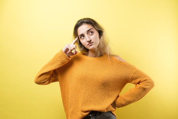 Il ritratto di una bella ragazza con un maglione arancione guarda da parte con un'espressione pensierosa