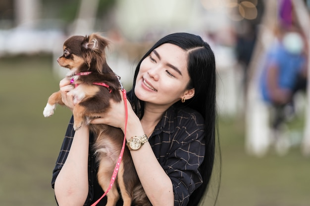 Ritratto di una bella ragazza che gioca con il suo adorabile cucciolo all'aperto nel parco pubblico. il cagnolino con il proprietario trascorre una giornata al parco giocando e divertendosi. foto d'archivio di amore per gli animali domestici