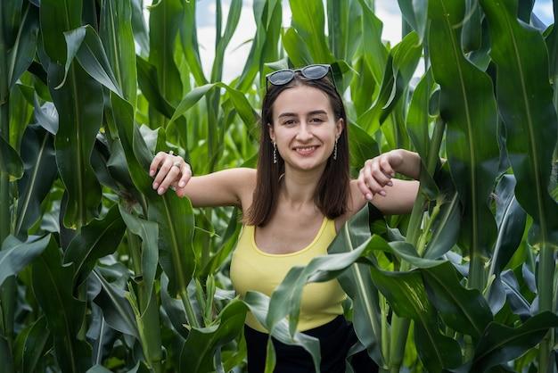 Ritratto di una bella ragazza in posa in un campo di mais verde, goditi il tempo libero estivo