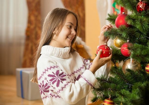 Ritratto di bella ragazza in maglione che decora l'albero di natale
