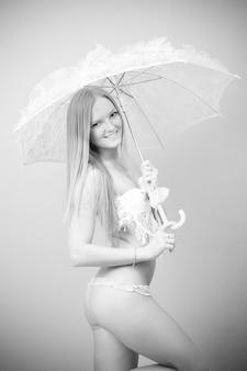 Ritratto di una bella ragazza in costume da bagno con ombrello di pizzo su sfondo grigio