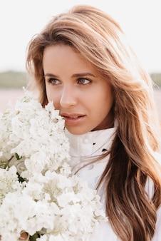 Ritratto di una bella ragazza in un abito bianco con un mazzo di fiori in un campo in estate
