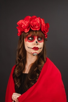 Ritratto di una bella ragazza con il trucco dia de los muertos ricoperta da un mantello rosso con sfondo grigio.