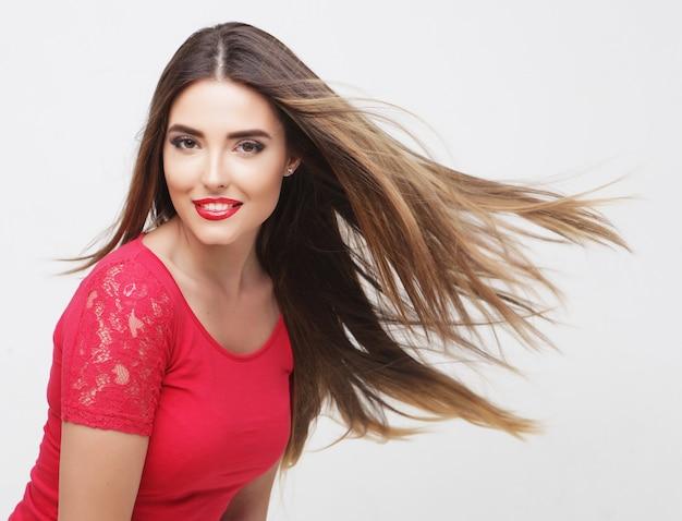 Ritratto di una bella ragazza con i capelli svolazzanti su sfondo bianco