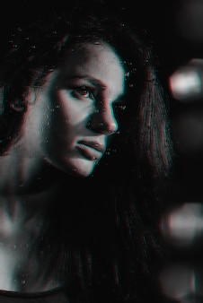 Ritratto di una bella ragazza con effetto glitch attraverso il vetro con gocce di pioggia