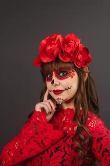 Ritratto di una bella ragazza con trucco e abbigliamento dia de los muertos su sfondo nero.