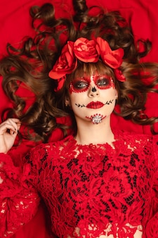 Ritratto di una bella ragazza con trucco e abbigliamento dia de los muertos sdraiato su uno sfondo rosso.