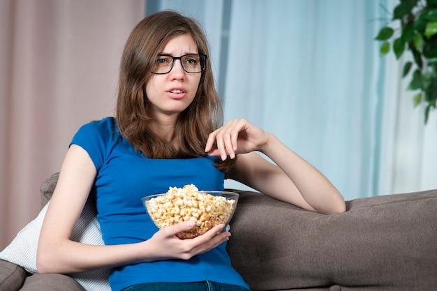 Ritratto di bella ragazza giovane donna triste sconvolta sta piangendo e guardando film di fiction tv tv