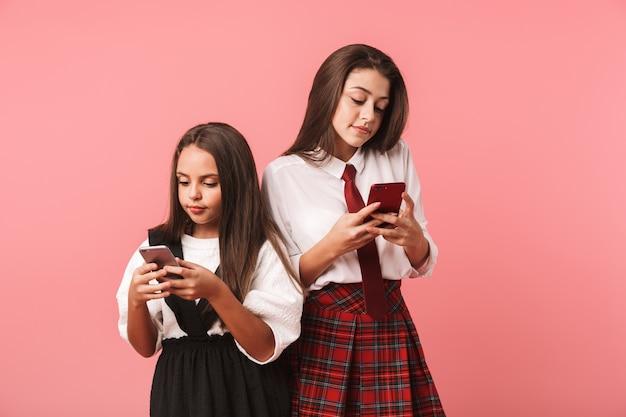 Ritratto di belle ragazze in uniforme scolastica utilizzando smartphone, mentre in piedi isolato sopra il muro rosso