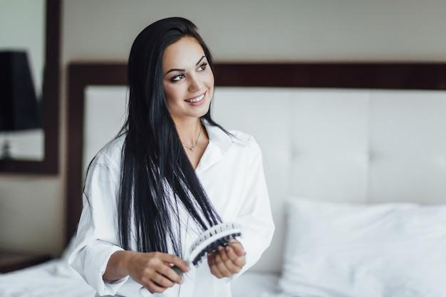 Ritratto di una bella ragazza bruna felice seduta a letto e che si rade i capelli con un fascino.