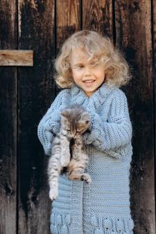 Ritratto di una bella e felice ragazza riccia in un maglione lavorato a maglia blu che gioca con un gattino vicino a una parete di legno