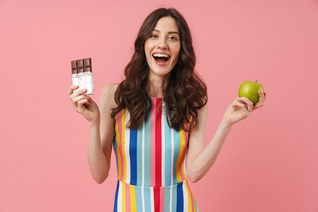 Ritratto di bella donna carina emotiva felice in posa isolata sul muro rosa che tiene mela e cioccolato