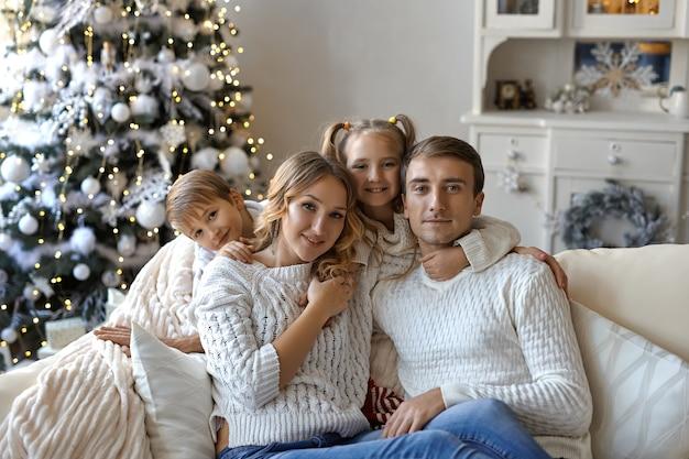Ritratto di bella famiglia felice con due bambini in maglioni bianchi seduti sul divano in una stanza decorata a festa con un albero di natale