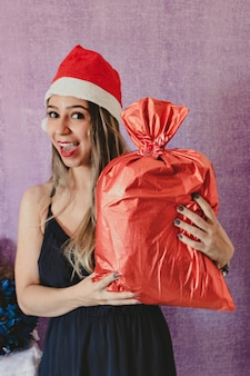 Ritratto di bella e felice sig.ra claus in cappello di natale che tiene un regalo di natale. isolato su uno sfondo viola.