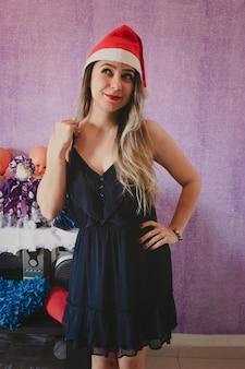 Ritratto di bella e felice signora claus in cappello di natale. isolato su uno sfondo viola.
