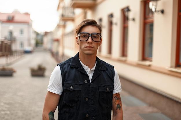Ritratto di un uomo bello hipster con occhiali e un giubbotto di jeans in città