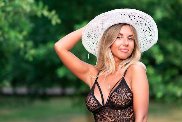 Ritratto di bella donna sexy calda, ragazza attraente sta camminando nel parco soleggiato in estate bianco paglia vimini elegante cappello bianco sulla sua testa e in costume da bagno di pizzo, biancheria intima, che guarda l'obbiettivo, sorridente