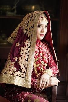 Ritratto di una bella sposa indiana in abito rosso e oro