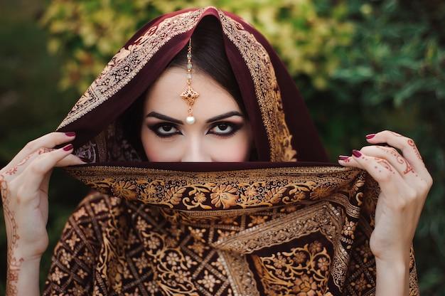 Ritratto di una bella ragazza indiana. modello di giovane donna indù con tatoo mehndi e gioielli kundan.