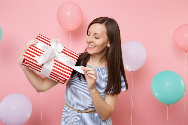Ritratto di bella donna gioiosa in abito blu che slega fiocco su scatola rossa con regalo presente su sfondo rosa pastello con mongolfiere colorate. festa di compleanno, concetto di emozioni sincere della gente.