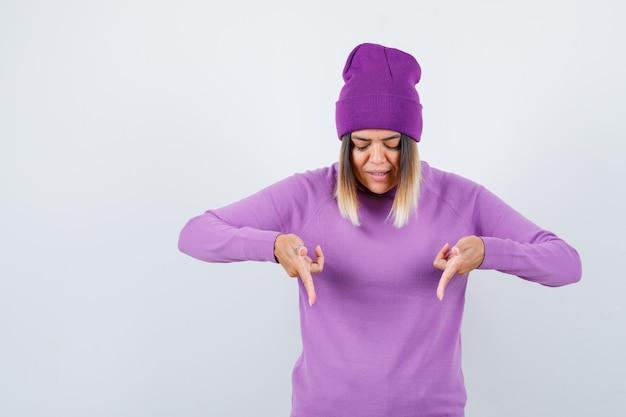 Ritratto di bella signora che punta verso il basso in maglione, berretto e guardando fiducioso vista frontale